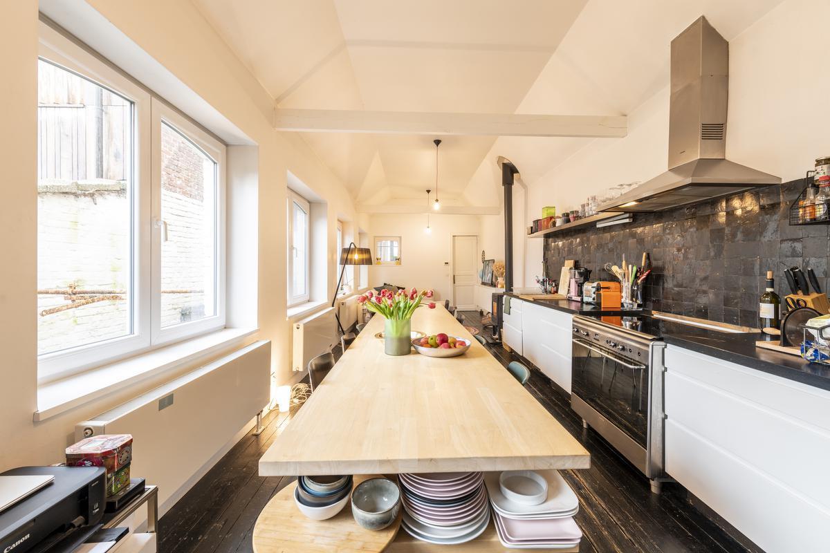 De lange eettafel in de keuken waar gasten mogen aanschuiven is op maat gemaakt.© Pieter Clicteur