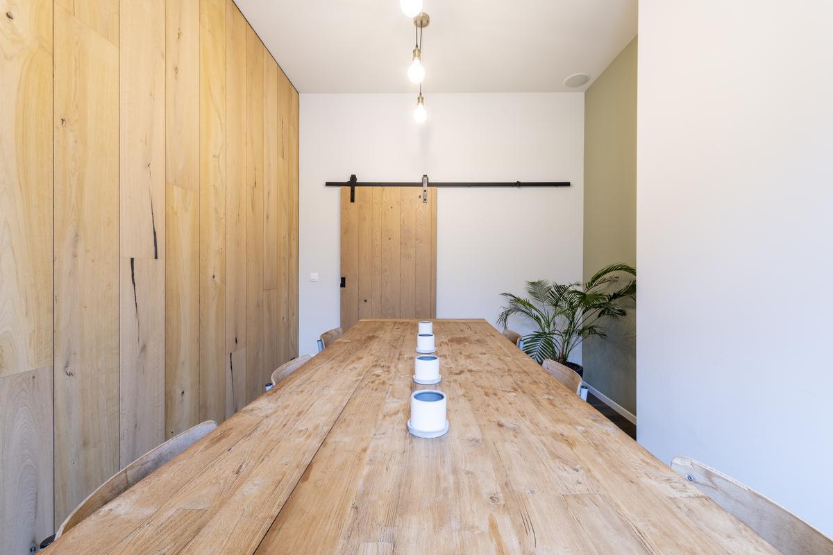 Gasten schuiven aan de lange houten tafel aan.© Pieter Clicteur