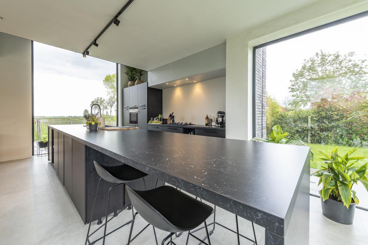 De zwarte keuken is een mooie eyecatcher tussen de witte muren.© Pieter Clicteur
