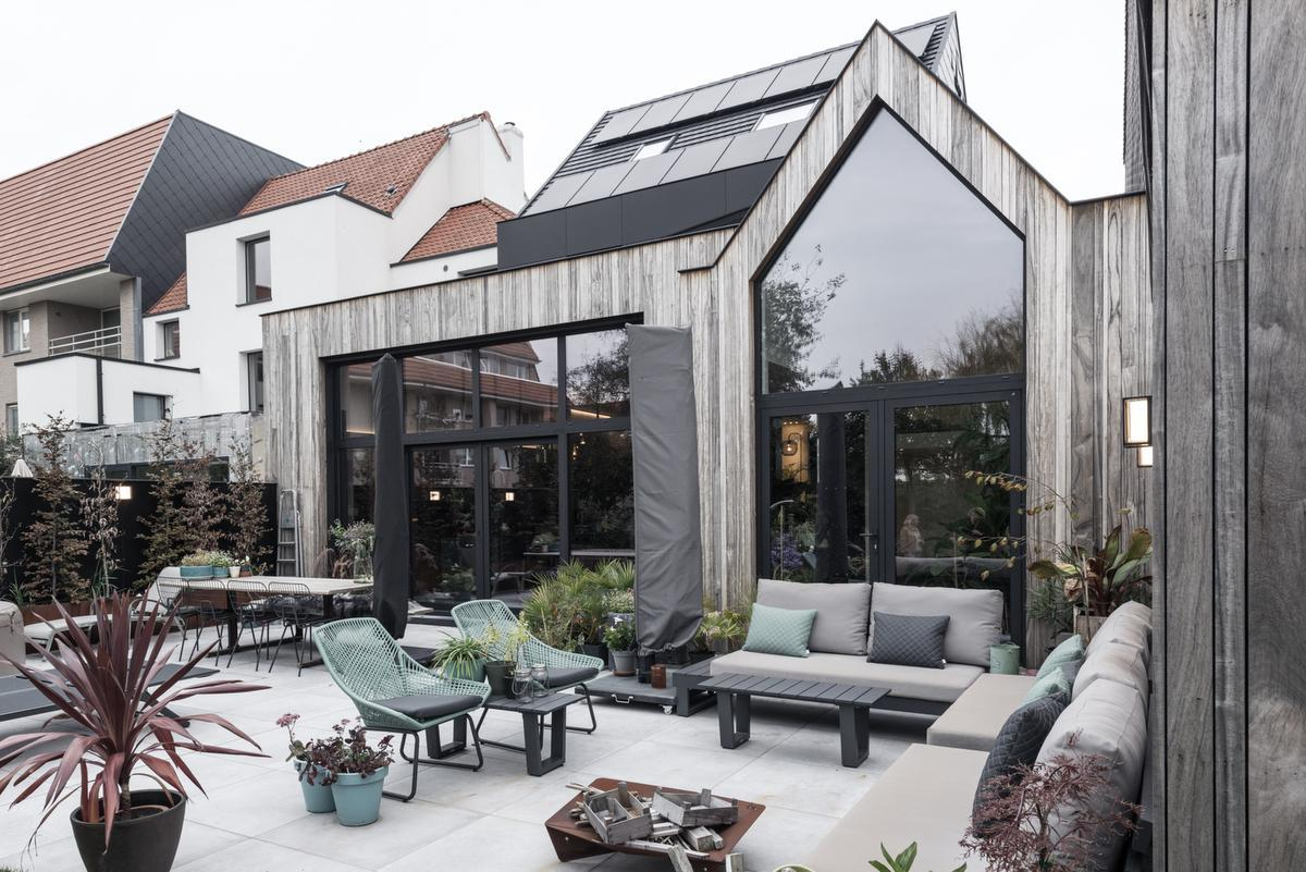 Modulaire tuinmeubels van Domus Plus geven karakter aan het terras. De vergrijsde padoek achtergevel en zachtgrijze tegels vergroten het ruimtegevoel met de keuken.© ARG Architecten