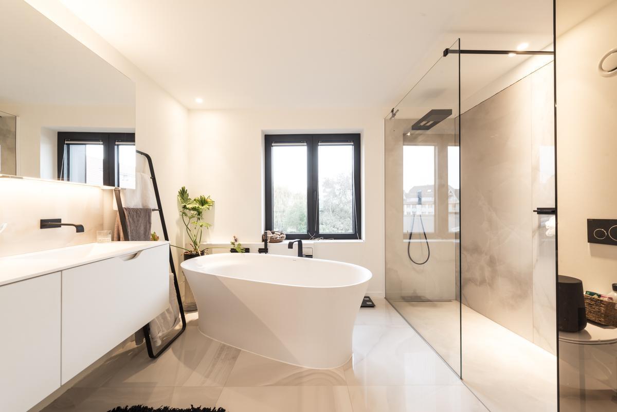 Zongekuste zandtinten en een glazen doorkijkwand geven de badkamer een onmisbaar wellnessgevoel in huis.© ARG Architecten