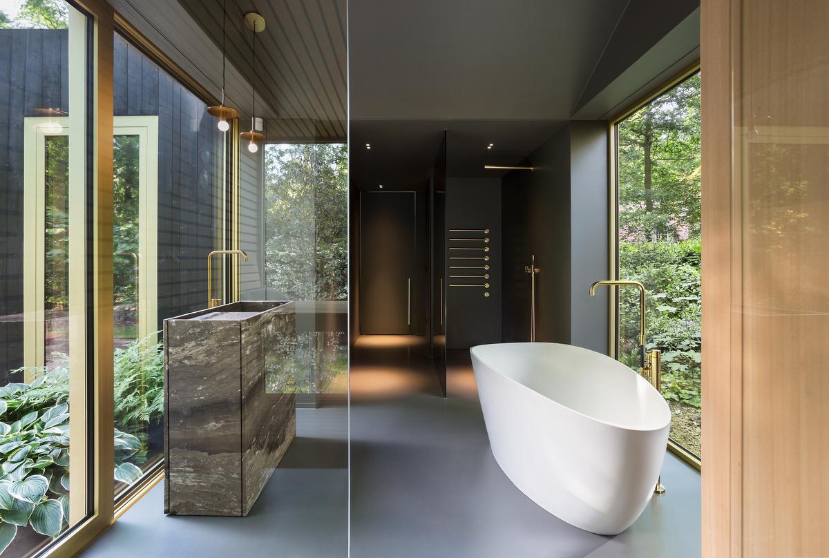 Een donkere vloer, plafond en douchewand creëren een intieme setting voor een badkamer met subtiele grandeur. De doorlopende ramen omkaderen de natuur.© Giulia Frigerio