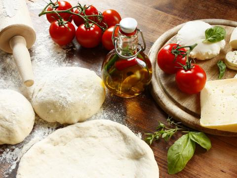 Italiaanse pizzabakker is acrobaat met pizzadeeg