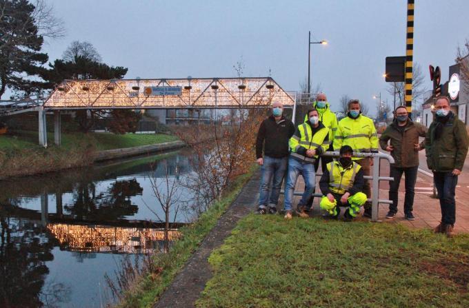 Schepen Wim Janssens (uiterst rechts) met zijn team van de Technische Dienst dat de voorbije dagen overal de kerstverlichting heeft geïnstalleerd, ook aan de voetgangersbrug in Adinkerke.©MYRIAM VAN DEN PUTTE MYRIAM VAN DEN PUTTE