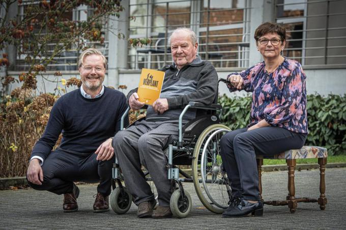 Frans Goethals met zijn exemplaar van 'Verplant'. Hij poseert tussen directeur Renaat en dochter Rita.©JOKE COUVREUR Joke Couvreur