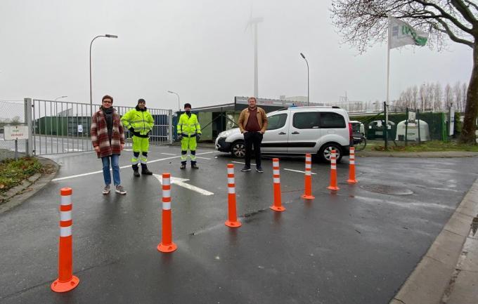 Schepen Caroline Maertens (links) en Dries Dehaudt (rechts), voorzitter van de Raad van Bestuur van IVIO met twee parkwachters aan het containerpark in Izegem. Door de aangebrachte paaltjes wordt het bestuurders die van de kant van de centrumbrug komen onmogelijk gemaakt om zo het containerpark op te rijden.
