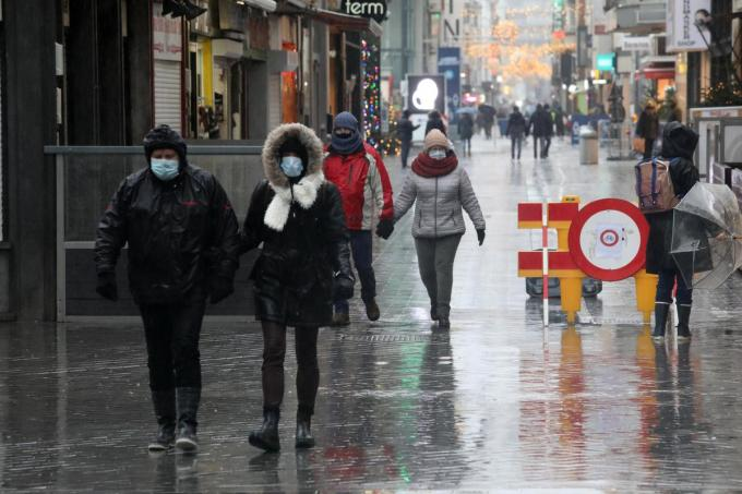 Goed ingeduffelde wandelaars trotseren het stormweer in de winkelstraat van Oostende.© Peter Maenhoudt