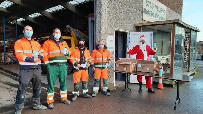 Benjamin Graulus en een deel van zijn groenteam krijgen hun thermosbeker uit handen van de kerstman.© (Foto JT)