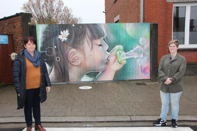 Directeur Lieve Dewitte en kunstenares Djoels sloegen de handen in elkaar voor de het graffitikunstwerk op de poort. (foto Jan)