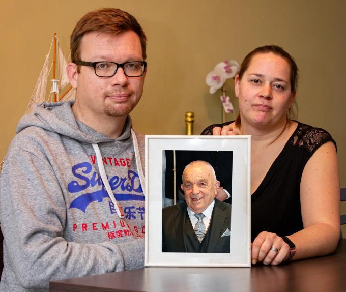 """Rino Veryser en zijn echtgenote bij een portret van zijn overleden vader. """"Zonder coronabesmetting leefde hij nu nog."""" (foto Kurt)©Kurt Desplenter Foto Kurt"""
