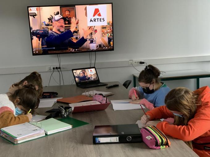 Leerlingen van 1B noteren ijverig de uitleg over de opdracht. Op de achtergrond legt Henk Rijckaert in het filmpje uit wat de opdracht inhoudt.© MVO