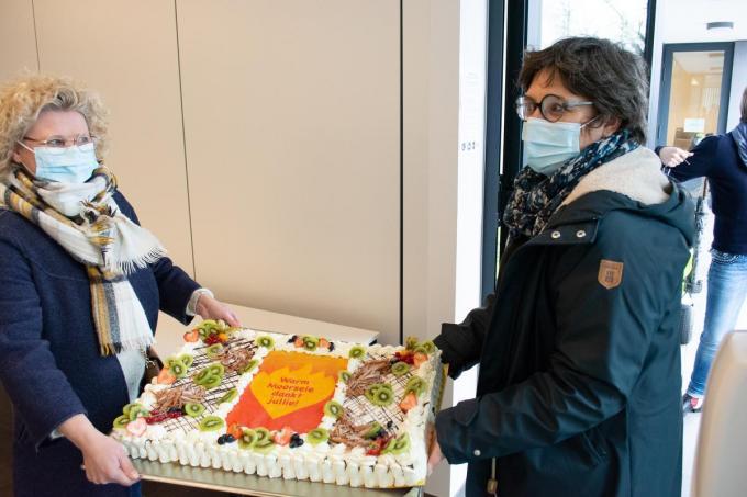 Katrien De Vlieger en Helle Lust, de voorzitters van Moorsele Onderneemt, dragen de taart binnen.© (Foto SLW)