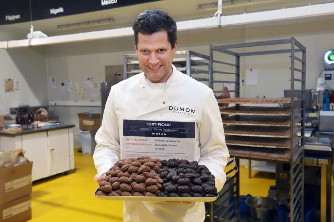 Jelle Descamps, zaakvoerder van Chocolatier Dumon, met de twee soorten Torhoutse Sparappeltjes: in melkchocolade en fondant.©Johan Sabbe