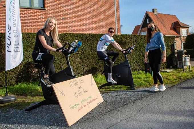 Bart en Petra zitten op de fiets, met Ellen Baar die toekijkt.© Davy Coghe