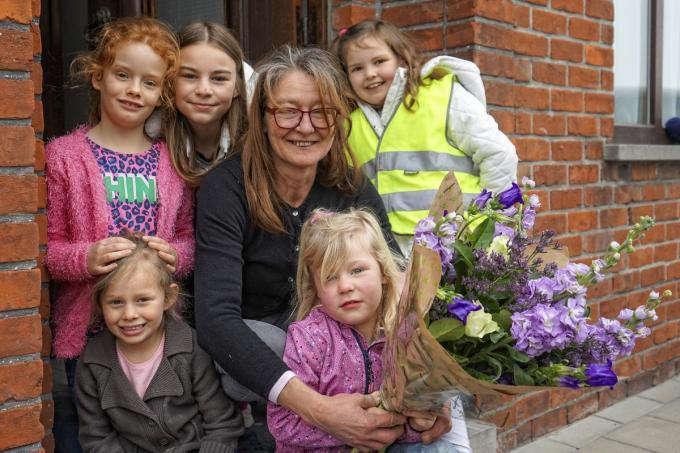 Pleegmoeder Mireille Seys met haar ruiker bloemen in het gezelschap van enkele van haar kinderen. (foto CLL)