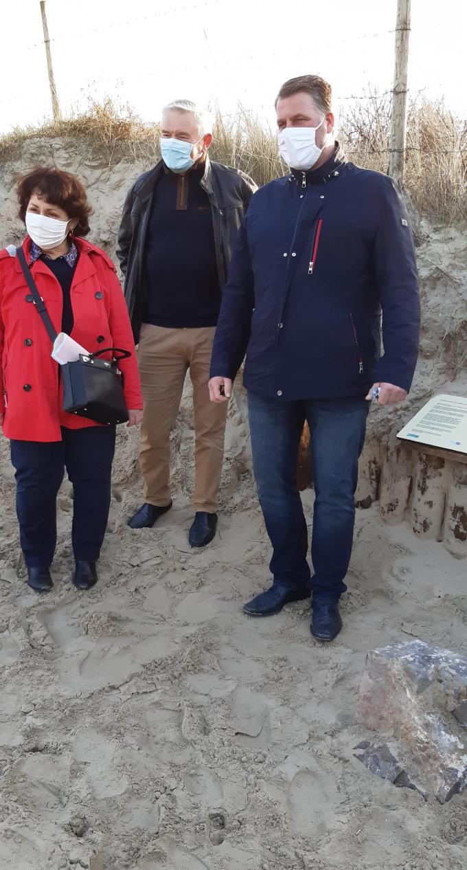 Burgemeester Christine Gilloots van Bray-Dunes en Bram Degrieck van De Panne bij de beschadigde grenspaal. Tussen hen in staat de heer Yves Hansenne van Bray-Dunes.© GF