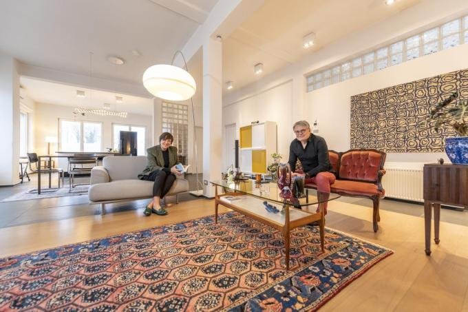 Ann en Bart in hun ruime living waar een Perzisch tapijt, gecombineerd wordt met een Chinees dressoir en fifties wandkast.© Pieter Clicteur