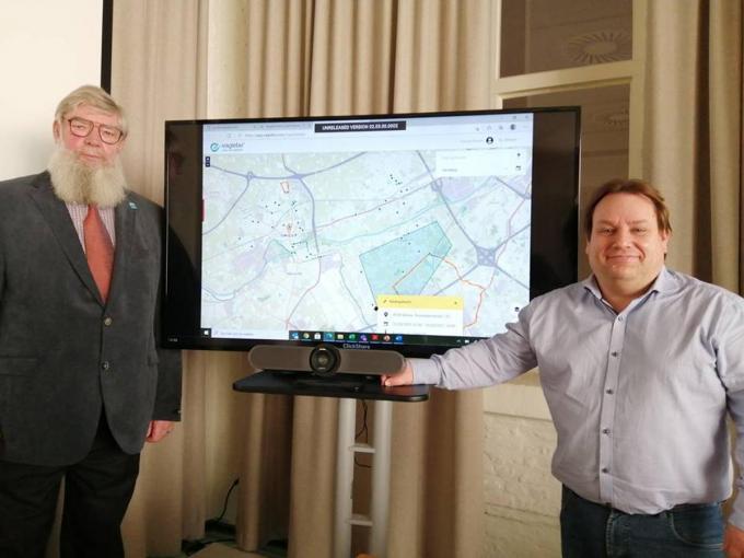 De schepenen Herman Ponnet en Patrick Roose leggen uit hoe de app werkt.© WO