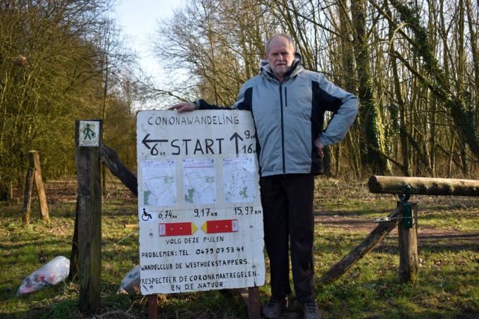Dirk Vangheluwe bij het bord dat de 'coronawandelingen aangeeft. (foto EG)