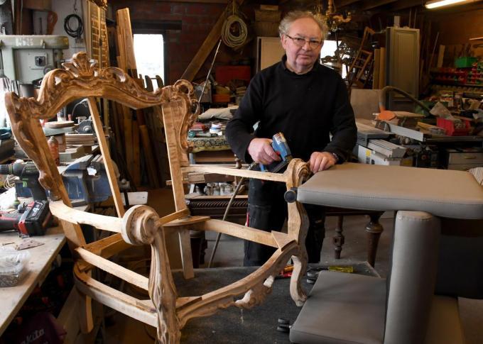 Ghislain met enkele meubels die hij restaureert in zijn atelier.© RB