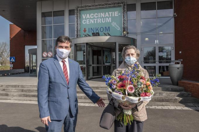 Burgemeester Kris Declercq overhandigde een boeketje aan Jacqueline, zij kreeg de 5.000ste vaccinatie in het Roeselaas vaccinatiecentrum.© Stefaan Beel