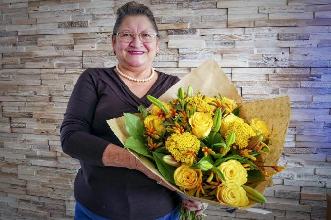 Moederkloek Rosa Salazar, een volbloed Ecuadoriaanse, is maar wat blij met de ruiker bloemen. (foto CLL)