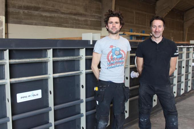 Ondernemers Wim Devreese en Denis Dierickx bij een bijna afgewerkte, kunststoffen badkuip in hun groot atelier aan de Spildoornstraat in Desselgem.© DJW