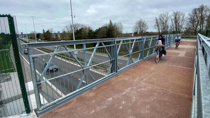 De eerste fietsers rijden over de nieuwe fiets- en voetgangersbrug over de A10 snelweg aan de Konterdam.© Peter Maenhoudt