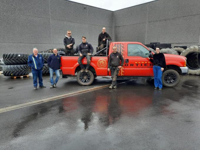 Het team van Banden Mortier met links Roland en Wim Mortier en Michiel Mortier zittend op de jeep omringd door werknemers Kevin 'Harry' Plets, Glenn 'Brommer' Tytgat en Davy 'Fritz' Devolder en rechts Sofie Devos.