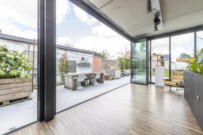 De hele linkerkant van de woonkamer bestaat uit grote harmonicaramen waardoor binnen buiten wordt en het huis in het licht baadt.© Pieter Clicteur