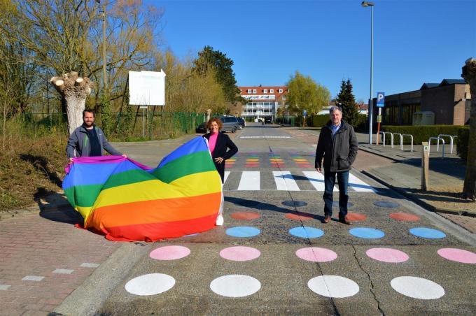 Schepen Mathieu Delbarge, schepen Marleen De Soete en burgemeester Wilfried Vandaele stellen trots het regenboogzebrapad voor.© WK