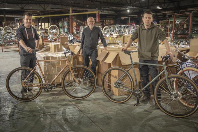Centaal staat pa Jan Oosterlinck, links zoon Tom met een fiets met verkoperd frame, rechts zoon Peter met het frame dat al tot kopergroen is geoxideerd.©Wouter Meeus