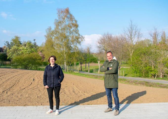 Schepen Annelies Vandenbussche en burgemeester Francis Benoit aan de kavel die straks een bloemenweide wordt. (foto AD)
