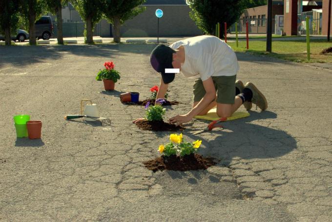 Een 'geheimzinnige' tuinier vult de valkuilen voor fietsers in de straten op.© foto TV