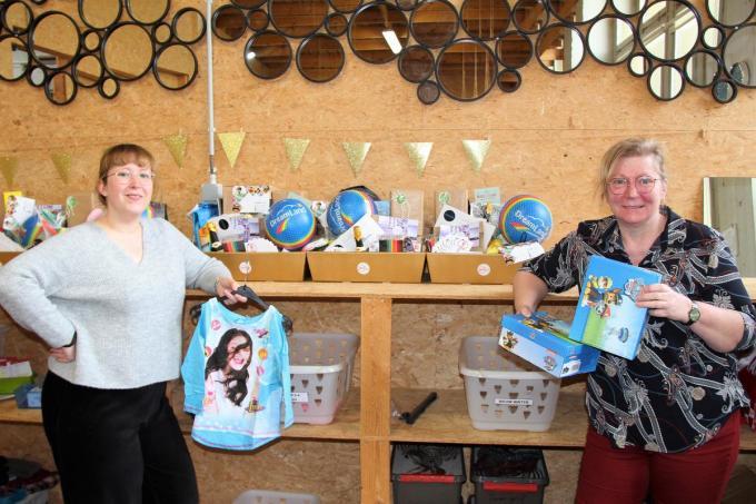 Magali Goeminne en Katrien Maes delen kledij en geschenkpakketten uit.© JVGK