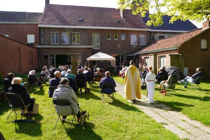 De gelovigen in de tuin van pastoor Rudi.© foto Luc