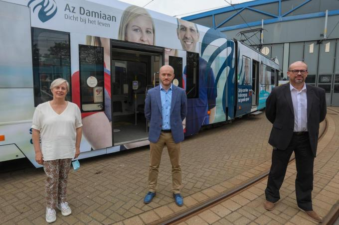 Directieleden van AZ Zeno, AZ Damiaan en AZ West voor een tram met foto's van zorgmedewerkers.©Peter MAENHOUDT