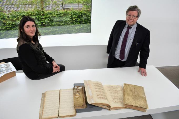 Archivaris Elisabeth Blancke en burgemeester Koenraad Degroote met twee gerestaureerde parochieregisters (rechts) en twee die nog moeten worden aangepakt.©TOM VAN HOUTTE