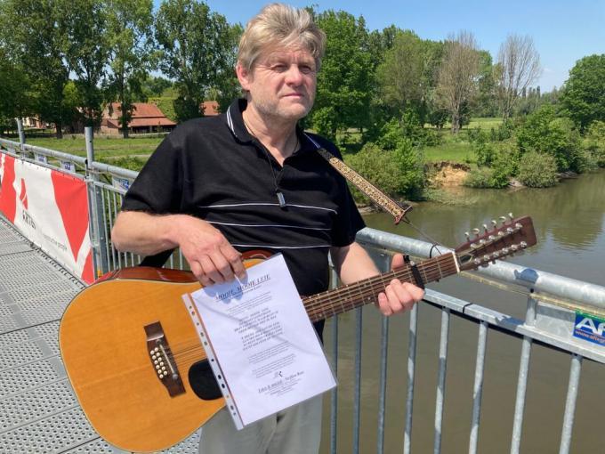 Steffen Ron aan de Leie-brug met liedteksten.