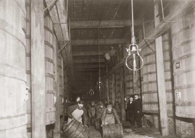 Een beeld uit een ver verleden: arbeiders rollen de gevulde vaten door één van de foederzalen.© GF
