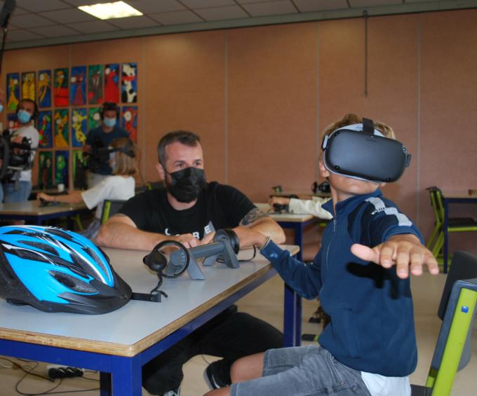 Onderzoeker en expert virtual reality-leren Carl Boel kijkt toe hoe een van de kinderen oefent met de VR-bril.© PDC