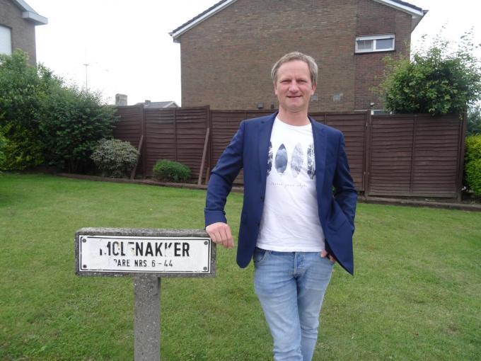 """Renzo Callant aan het onleesbare straatnaambord in de wijk Molenakker. """"Een inventarisatie en aanpassing van de straatnaamborden is absoluut noodzakelijk."""" (foto TV)"""