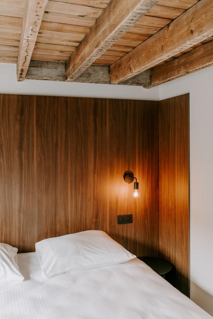 In de slaapkamers werden de houten balken in het plafond bloot gelaten om het ruimtegevoel en karakter van het huis uit te lichten.(foto Margo Carton)