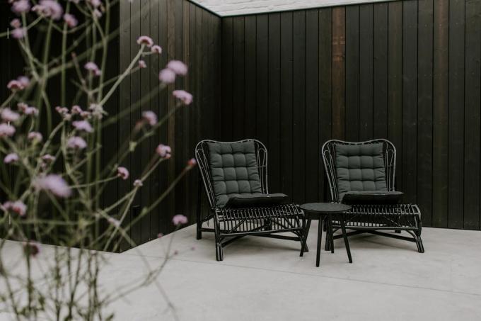 De zwarte rotan Colony-loungstoelen van House Doctor creëren een relaxte sfeer op de mediterrane patio.