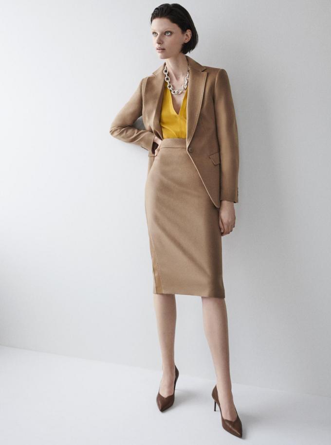 Tijdloos mantelpakje bestaande uit een blazer (559 euro), knielange kokerrok (279 euro) en chemisier (279 euro), schoenen (419 euro) en juweel (139 euro) van Max Mara.