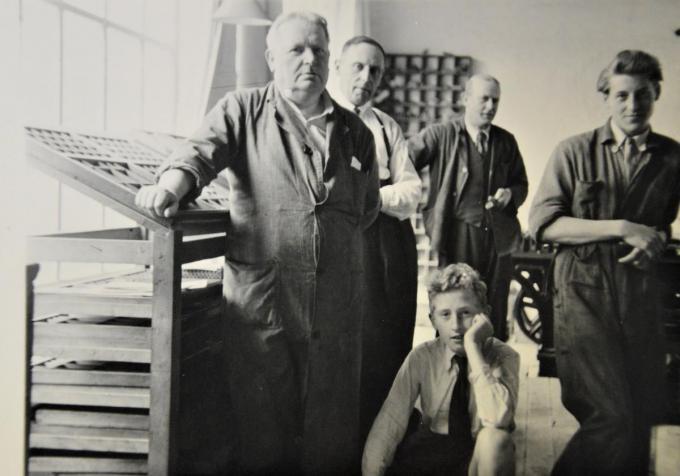 Jules (uiterst links) en Jozef (gehurkt) in de drukkerij omstreeks 1947.