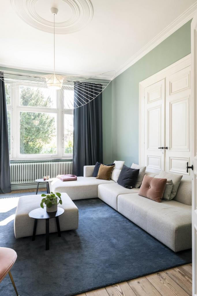 De Vertigo-hanglamp van Petite Friture is een elegante eyecatcher in de woonkamer. Het ontwerp van Constance Guisset wordt gevormd door bijna gewichtloze linten van kunststof en creëert een patroon van zachte schaduwen op de muren en comfortabele zitbank van Prostoria.