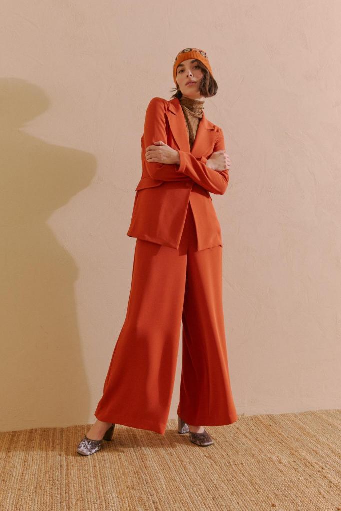 Blazer (318 euro) en wijde broek (210 euro) in een warme herfsttint, fluwelen pumps (365 euro), van Maliparmi.