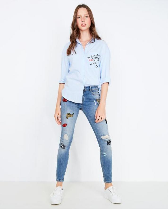 Le jean brodé décoré d'écussons