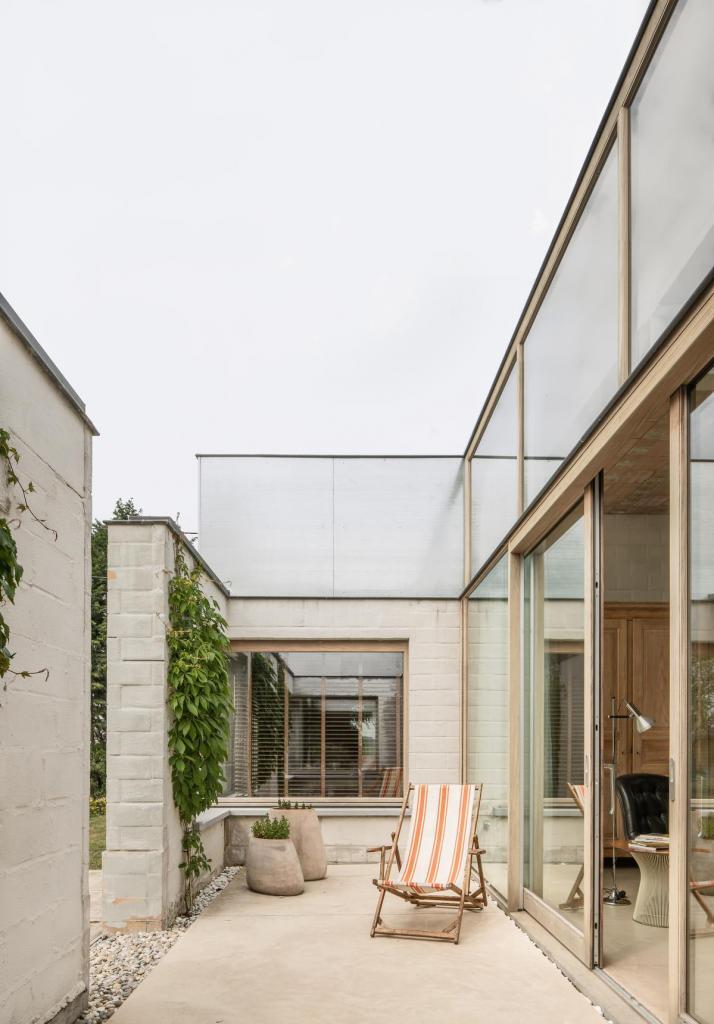Om het binnen-buitengevoel en de ruimtelijkheid van de bungalow te versterken, is de aangrenzende patio afgebakend door een muur van het oorspronkelijke bijgebouw, met dezelfde raamopeningen als de bestaande woning.